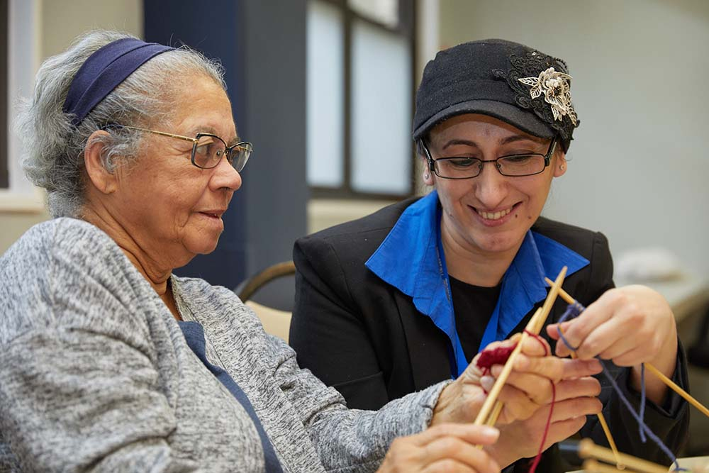 nurse teaching senior patient how to knit