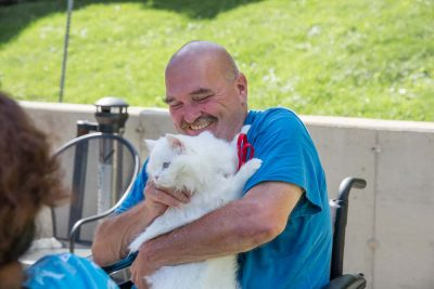 Happy patient playing with his cat after being treated by total parenteral nutrition in foresthills queens