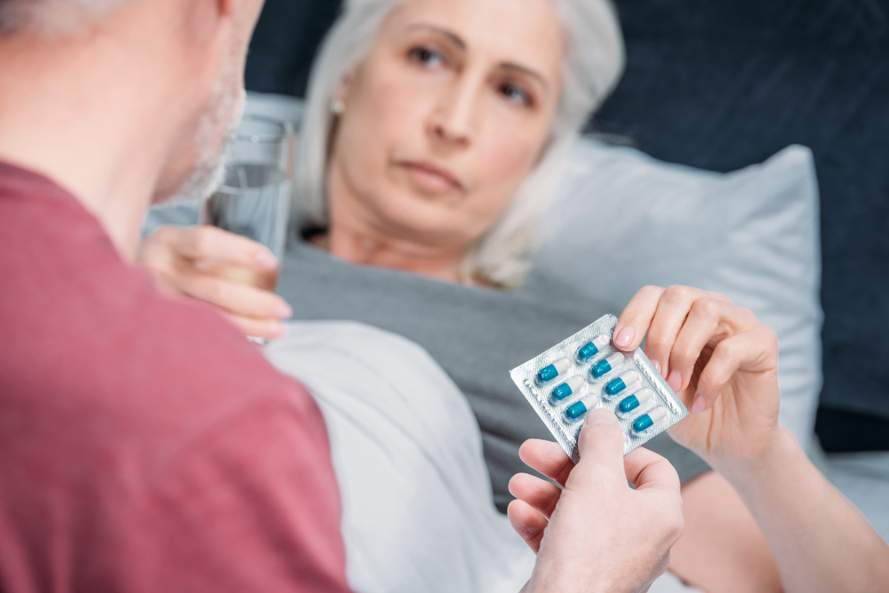 Elderly women taking medicine for infectious disease care