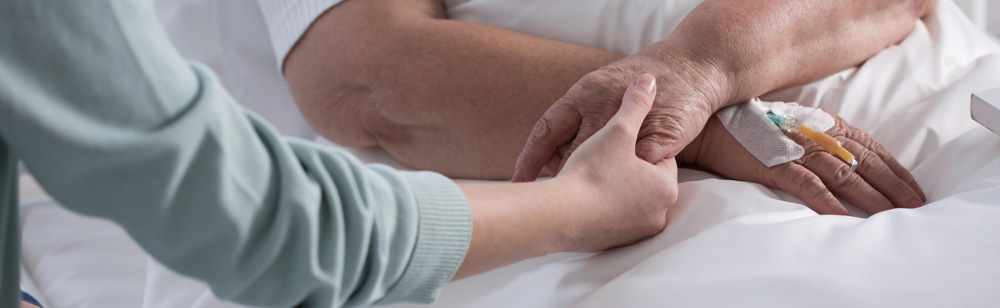 Nurse holding patients hand and providing palliative care at Fairview Rehab & Nursing Home
