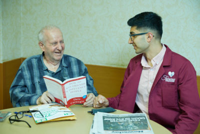 An elderly patient smiling while reading the book as a part of recreation therapy to prevent memory loss