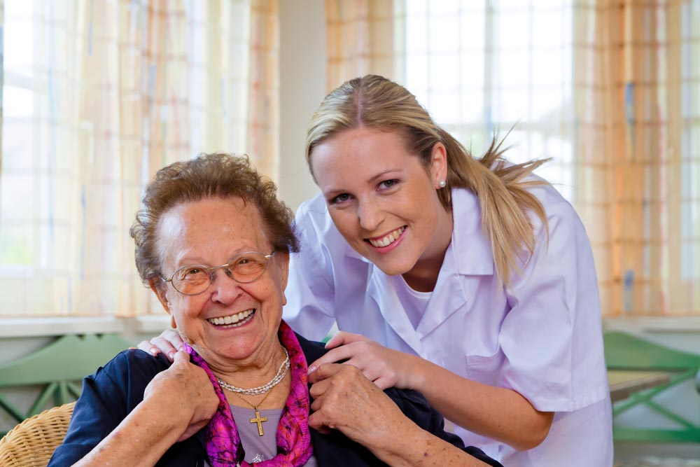 Nurse providing post surgery care to an elderly lade in a nursing home