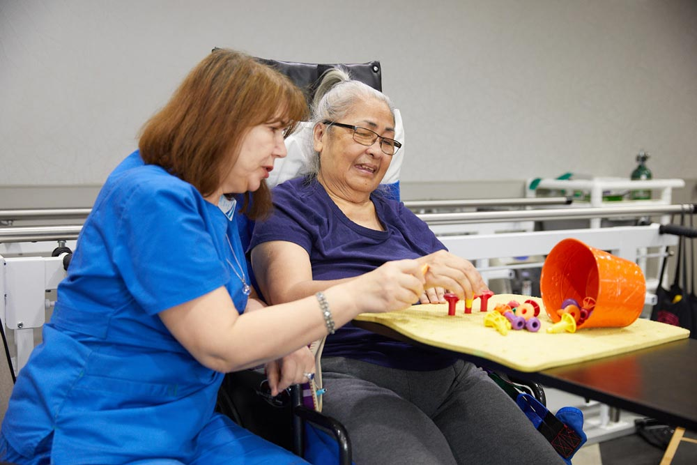 An elderly woman getting occupational therapy at Fairview Rehab