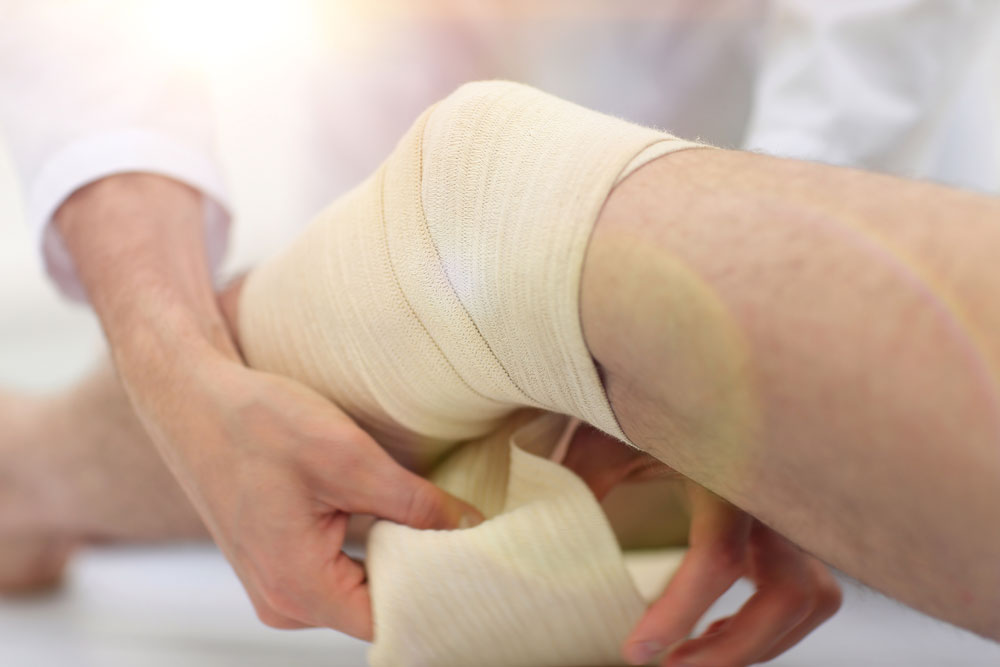 Doctor bandaging patients leg to speed up wound healing