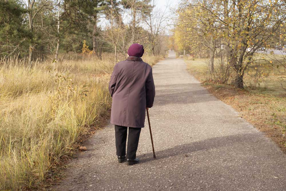Elderly women suffering from dementia wandering on a lonely road