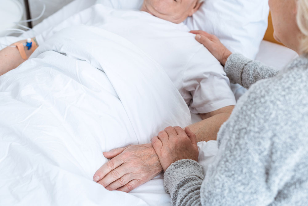 Senior woman holding elderly man's hand suffering from bedsores