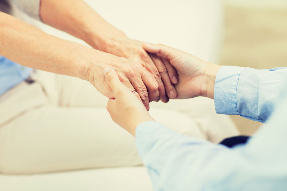 Nurse holding hands of a senior woman suffering from substance abuse conditions