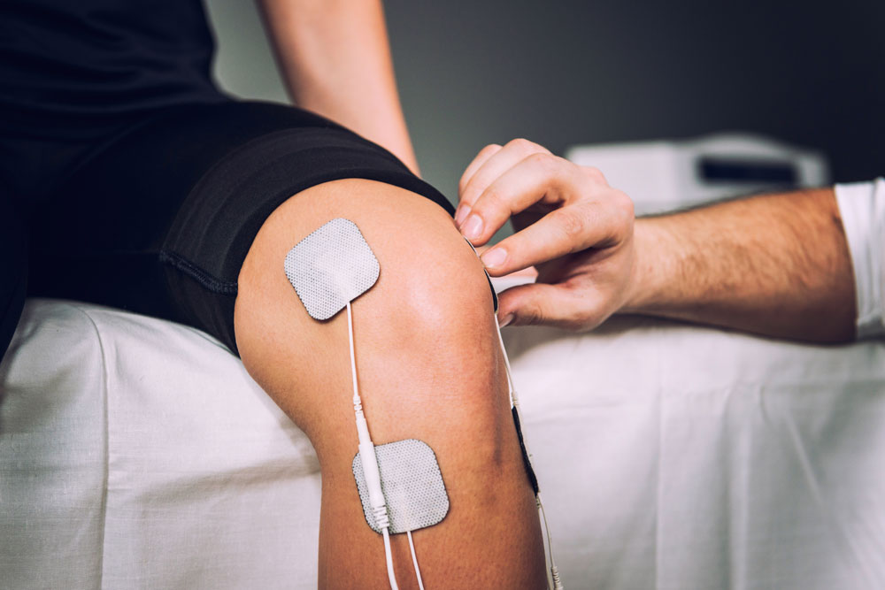 Electro stimulation as a part of physical therapy used to eliminate chronic knee pain