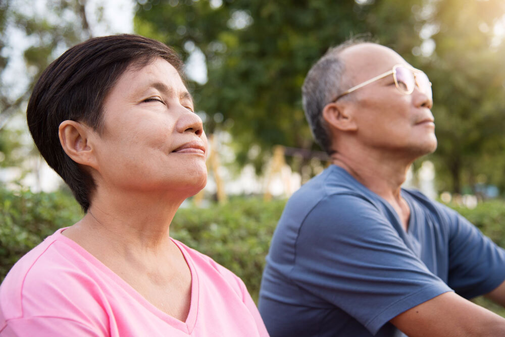 Asian senior couple doing breathing exercise in open and natural air