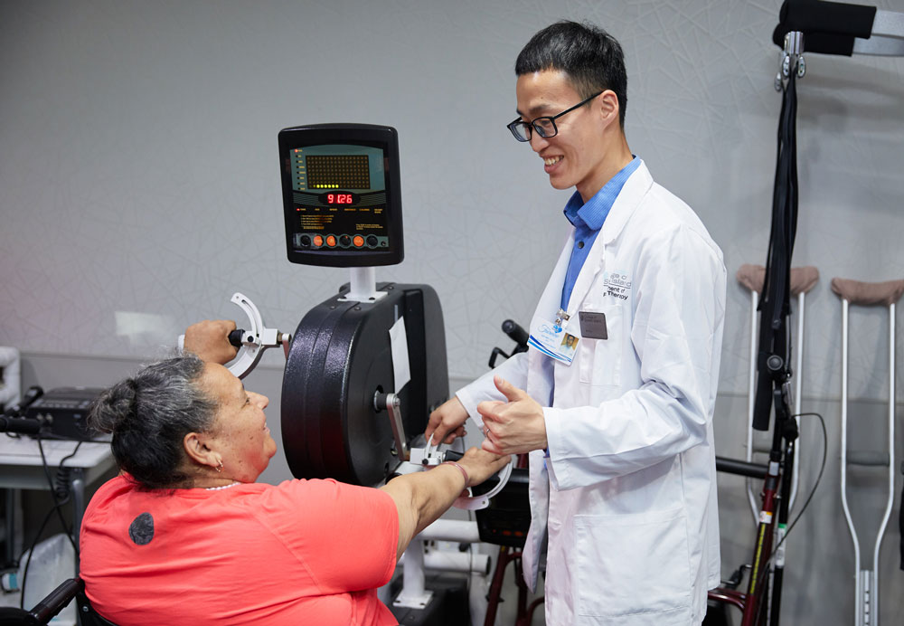 Therapist helping elderly woman in physical therapy after surgery to speed up the recovery
