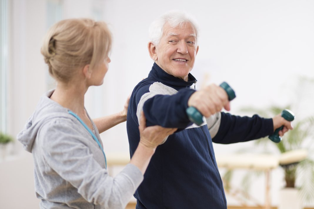 Therapist helping elderly man with exercise during short-term rehab program