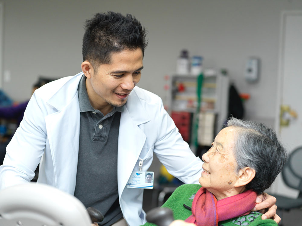 Male nurse providing wound treatment and care to an elderly woman