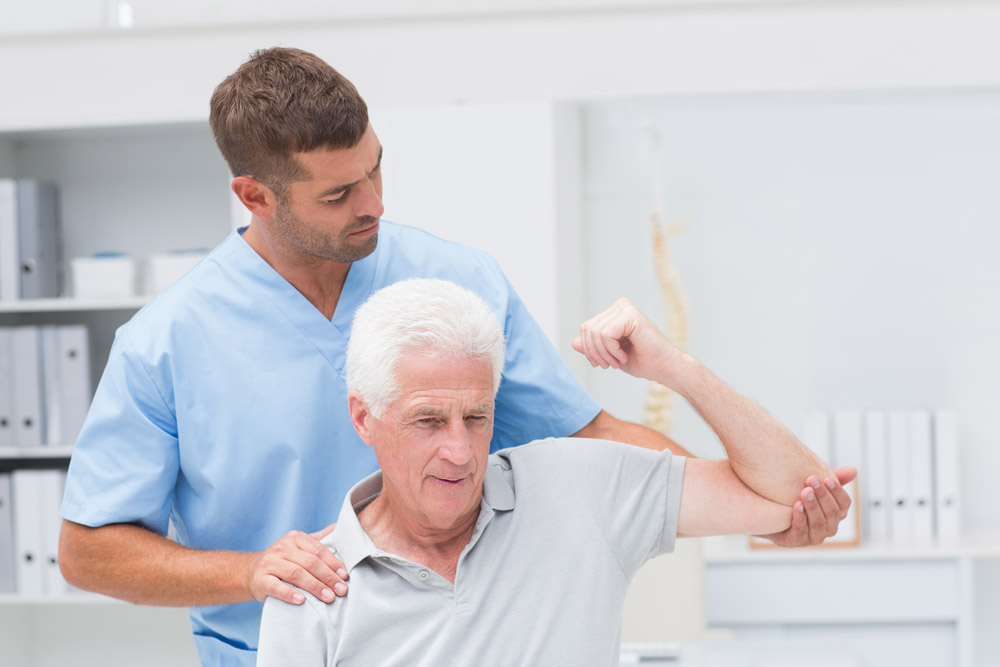 Physiotherapist giving physical therapy to elderly man suffering from shoulder pain