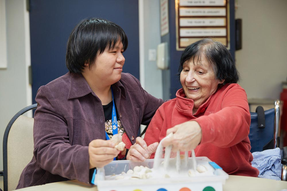 Therapist providing occupational therapy to elderly woman to regain motor skills