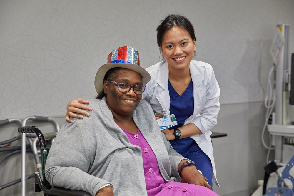 Elderly black woman smiling with rehab nurse after getting multiple sclerosis rehab