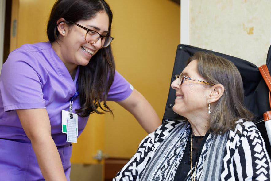 Nurse providing wound care to an elderly woman